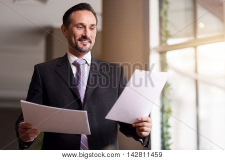 Ready to work. Cheerful delighted senior man smiling and holding papers while working