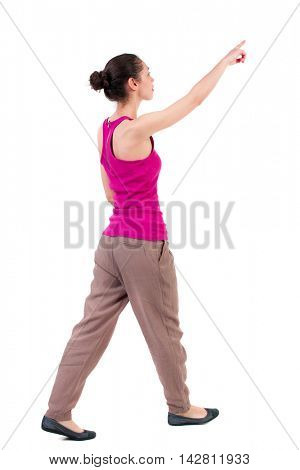 back view of pointing walking  woman. going girl pointing.  backside view of person.  Rear view people collection. Isolated over white background. dark girl walks slowly to the side pointing up.