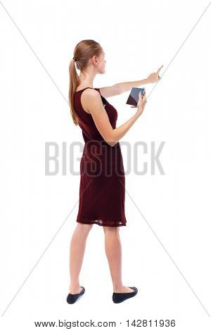 back view of pointing young beautiful  girl with tablet computer. girl  watching. Rear view people collection.  backside view of person.  Isolated over white background. Slim blonde in a burgundy