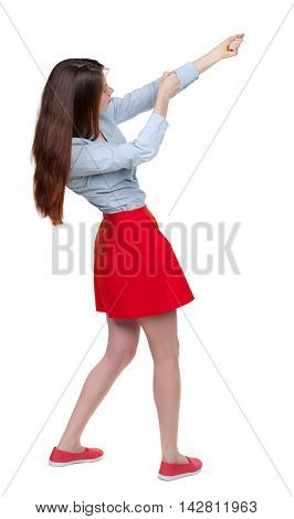 back view of standing girl pulling a rope from the top or cling to something. girl  watching. Rear view people collection.  backside view of person.  Isolated over white background. Long-haired