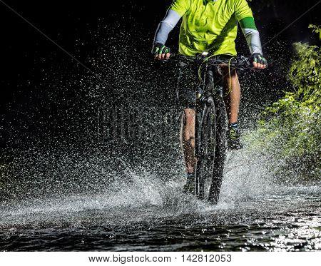 Mountain biker at night riding through forest stream and splashing water around. Front-view