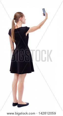 back view of standing young beautiful  woman  using a mobile phone. girl  watching. Rear view people collection.  backside view of person.  Isolated over white background. Blonde in a short black