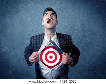 Businessman tearing his shirt off with target sign symbol on his chest concept on background