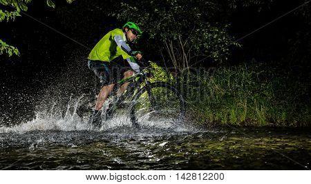 Mountain biker at night riding through forest stream and splashing water around. Side-view