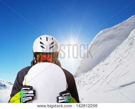 Snowboarder holding his snowboard off piste, beautiful winter landscape panorama on background