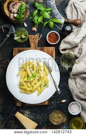 Italian pasta dinner. Penne with pesto sauce and fresh basil, Parmesan cheese and spices on rustic wooden board over dark grunge plywood background, top view, vertical composition