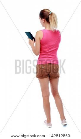 back view of standing young beautiful  woman using a mobile phone or tablet computer. girl  watching. Rear view people collection.  backside view of person.  Isolated over white background. Sport