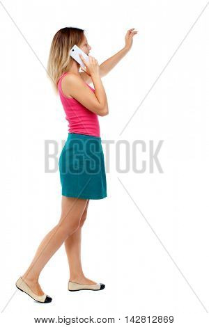 side view of a woman walking with a mobile phone. back view ofgirl in motion.  backside view of person.  Rear view people collection. Isolated over white background. Blonde in a red sweater and green