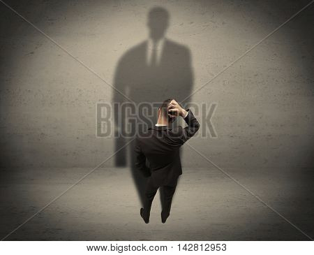 A young beginner salesman standing in front of a wall, facing his shadow as his boss or a successful businessman he lloks up to concept