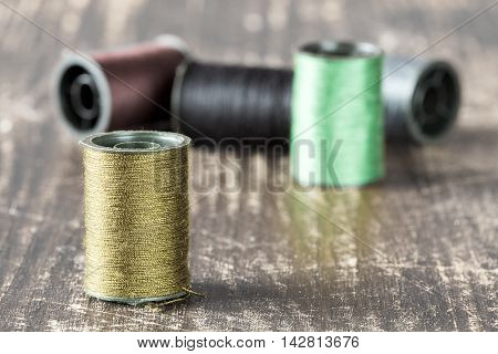 Bobbins with threads on old wooden table background