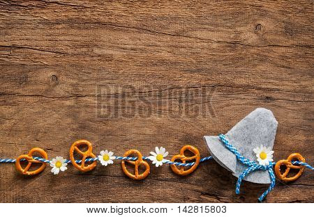 Border of pretzels and daisies with Bavarian hat on rustic wooden background with copy space for Oktoberfest
