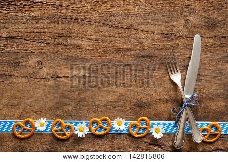 Border of pretzels and daisies with Bavarian cutlery  on rustic wooden background with copy space for Oktoberfest