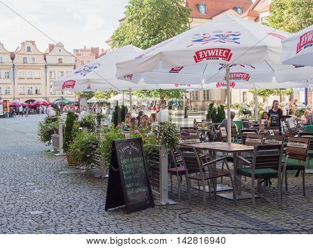 JELENIA GORA POLAND - AUGUST 13 2016: Tourists At A Cafe At Townhall Square in Jelenia Gora Poland