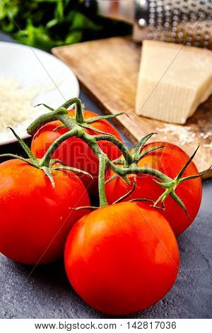 Branch of fresh red tomatoes with water drops on and parmesan or parmigiano reggiano cheese on back with grater and grated cheese on white plate and mint beam. Concept of italian cuisine ingredients