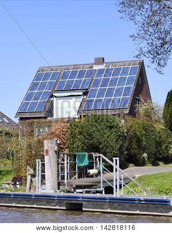 Solar energy efficient house on a pier, river scene.