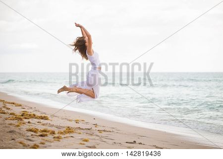 Young woman in a white dress jumping on the beach by the ocean. Happy vacation. Beach girl has fun by ocean. Excited girl jumping on white sand by beautiful blue sea.