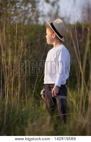 Adorable kid boy in straw hat standing on a summer meadow and looking into distance. Sunset in the park. Outdoors. Vacations.