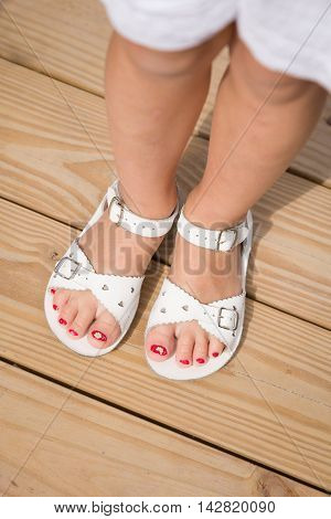 Closeup of girl's feet in white sandals on the wooden floor. funny red nails. Summer time. Vacations.