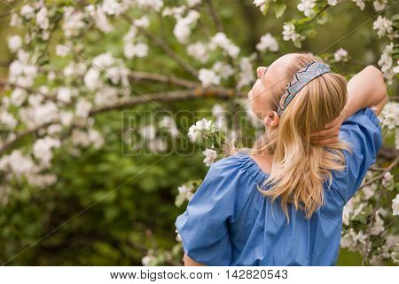 Portrait of a young smiling woman looking at apple trees' flowers. Girl and blooming apple tree. Spring time with trees flowers.