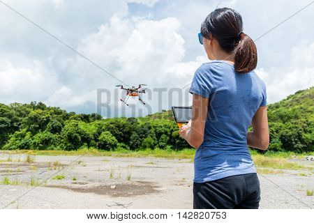 Woman controlling the flying drone