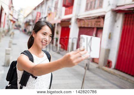 Woman using digital camera for taking selfie
