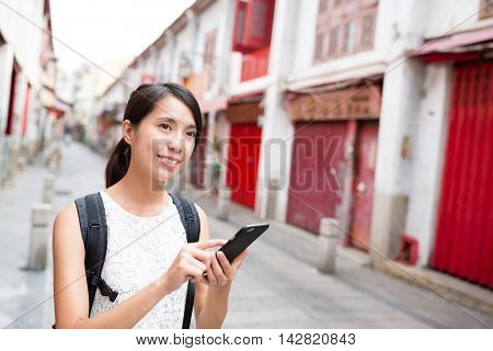 Woman searching something on mobile phone in Rua da felicidade