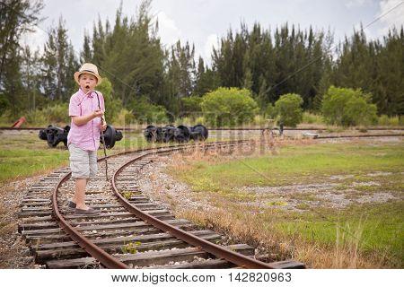 Cute kid boy in straw hat goes on railsin field in the summer. Child walking along old railroad.