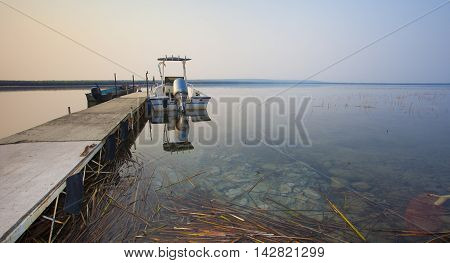 Dock with a pair of fishing boats tied up in Saskatchewan Canada