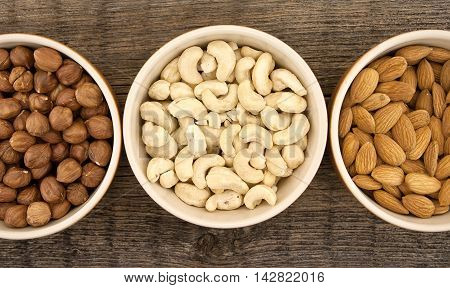 Almonds, Cashew And Hazelnuts In Ceramic Bowls On A Rustic Wooden Background. Top View. Healthy Conc