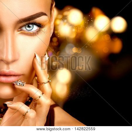 Beauty Fashion woman with Golden Makeup, gold accessories and nails. Girl Portrait with gold rings and manicure with crystals closeup isolated on black background. Fashion art make up