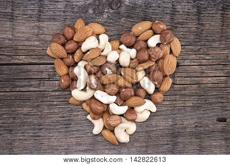 Shape Of Heart Made From Almonds, Cashews And Hazelnuts On A Rustic Wooden Background. Top View. Hea