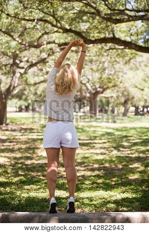 Back view on a blond woman stretching in the sunny park. Relax in the summer park outdoors. Healthy lifestyle. Vacations.