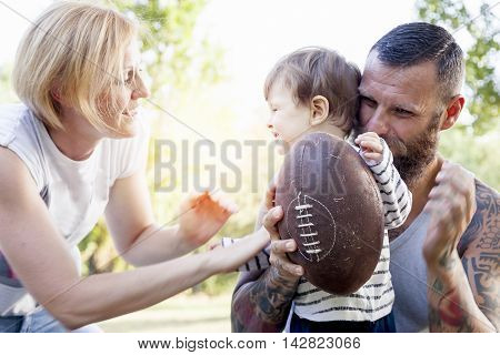 young couple with child having fun at the park with rugby ball