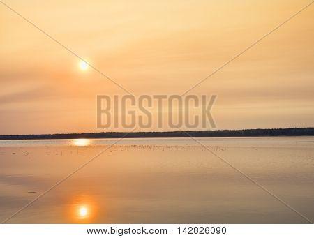 Sun high above the water at sunrise in Saskatchewan Canada