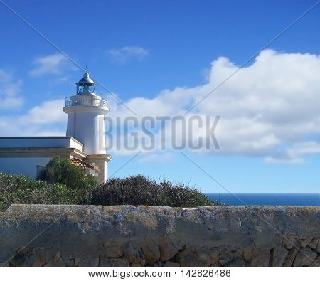 Beacon or lighthouse on a cliff with cloudy sky.
