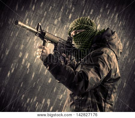 Close up of an armed terrorist man with mask on rainy background