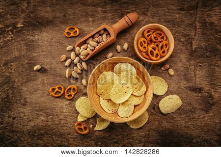 Potato chips, pistachio and salted crackers, top view