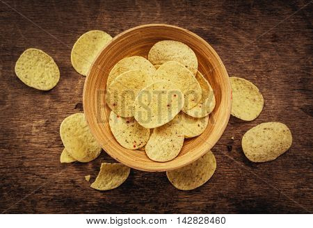 Crispy potato chips in bowl on wooden background. Closeup. Food background, top view