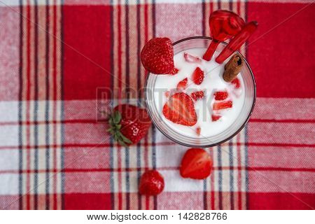 Milk Cocktail, Red Fresh Strawberries with Plastic Spoons and Cinnamon on the Check Tablecloth