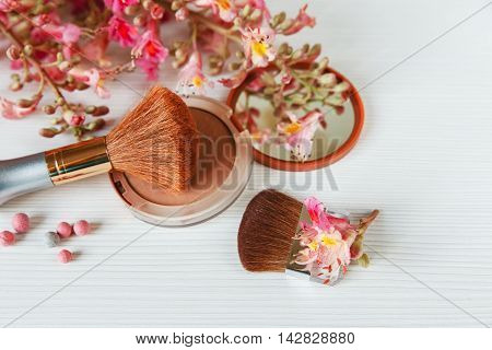 The Pink  Branches of Chestnut Tree,Bronze Powder with Mirror and Make Up Brush are on White Table