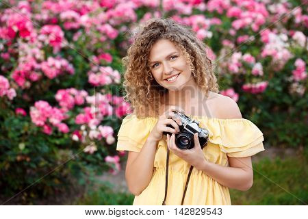 Young beautiful photographer in yellow dress smiling, looking at camera, walking around city.