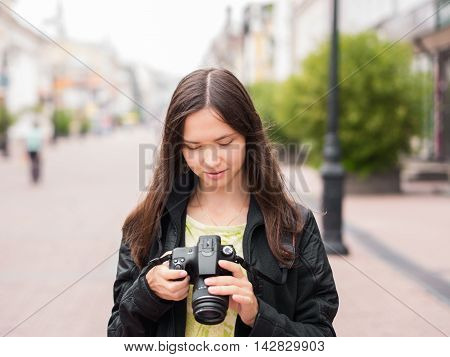 Cheerful young woman tourist watching shots in her dslr camera outdoors. Vacation photography travel concept