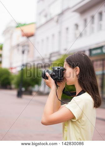 Cheerful young casual woman tourist make shots on dslr camera outdoors on city street. Vacation photography travel concept
