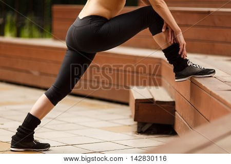 Fitness woman stretching legs before training outdoors, image lower body