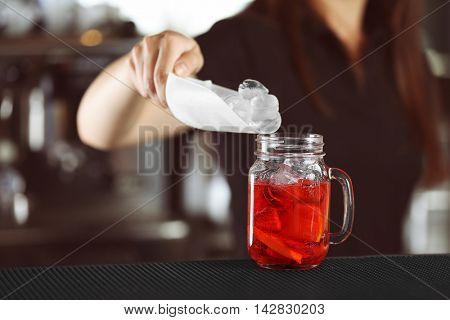 Woman hands adding ice into cocktail on bar counter