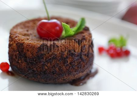 Delicious fondant with cherry and red currant on plate, closeup