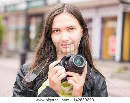 Woman on vacation photographing with dslr camera on city street. Looking at camera. Vacation photography travel concept