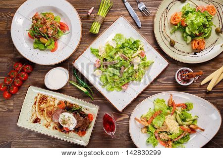 Different salads on wooden table, top view. Vegetable salad, Salad with smoked salmon, Baked meat with vegetables. Food background, Top view