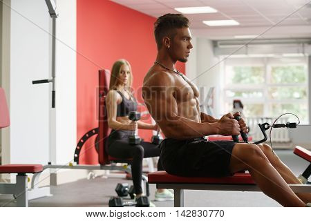 Shirtless guy trains on simulator and girl looks at him