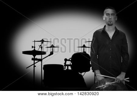 Young bearded drummer on drums silhouette background. Black and white photography